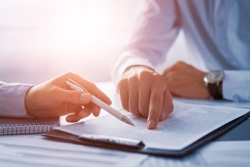 An attorney reviewing a drug injury claim with a cient.