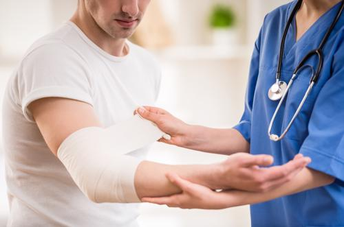 A man having an elbow injury treated by a medical professional.