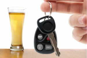 Hand holding car keys next to a glass of beer