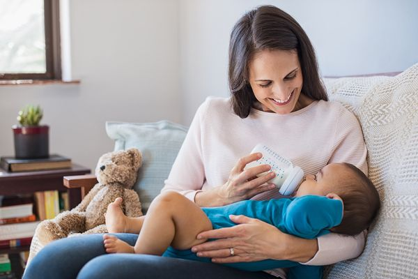 mother feeding child infant formula
